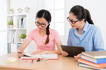 Foto de smiling elegant family teacher woman using mobile digital tablet to teach female student studying and preparing school exam. - Imagen libre de derechos