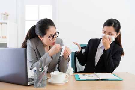 Photo pour attractive beauty girl company employee having disease problem coughing and female co-worker provide medical mask for her in order to avoid infection. - image libre de droit