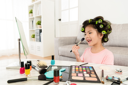 Photo pour happy lovely little girl children looking at mirror and using cosmetic brush makeup by herself in living room. - image libre de droit