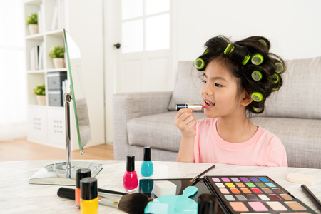 Foto de cute beautiful little girl kid using lipstick makeup. - Imagen libre de derechos
