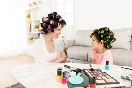 Foto de happy mother holding mirror for smiling cute little daughter looking beauty face when they finished makeup in living room. - Imagen libre de derechos