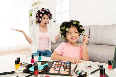 Photo pour happy young girl children looking at mirror using cosmetics brush painting eyeshadow and her mother in back feeling dumbfounded. - image libre de droit