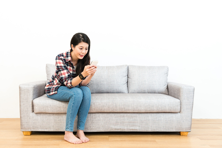 Foto de smiling young woman sitting on wooden floor sofa couch relaxing and using mobile cell phone chatting with friend in white background. - Imagen libre de derechos