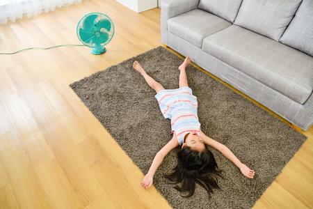 Photo pour high angle view photo of lovely attractive little girl lying down on carpet sleeping resting and blowing electric fan enjoying cool wind during summer season. - image libre de droit