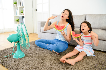 Foto de young mother with cute little daughter feeling hot in summer sitting on living room floor blowing electric fan refreshing and eating cold watermelon. - Imagen libre de derechos