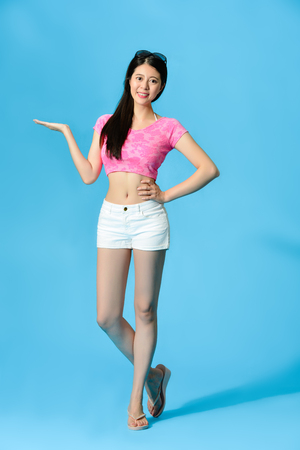 Photo for Beautiful young lady wearing summer clothing standing in blue background and face to camera making presenting gesture showing empty area. full length photo. - Royalty Free Image