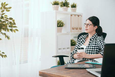 Photo for happy beautiful soho business woman holding coffee cup looking at window daydreaming when she working at home in workspace. - Royalty Free Image