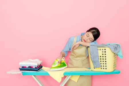 Foto de attractive elegant woman worker standing in pink background ironing feeling tired and sleeping on laundry basket resting. - Imagen libre de derechos
