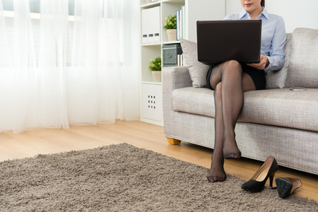 Photo for professional young business woman after work back to home take off high heel shoes relaxing and sitting on sofa using mobile laptop working. - Royalty Free Image