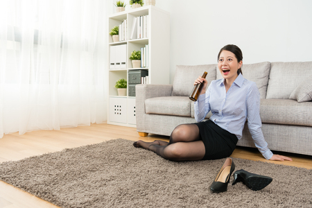 Photo for happy elegant female office manager sitting on floor watching tv and drinking beer to relax when she after work back to home. - Royalty Free Image