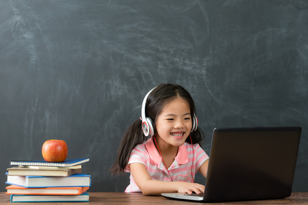 Photo for cheerful young little girl children using laptop computer with headphones studying through online e-learning system in chalkboard background. - Royalty Free Image