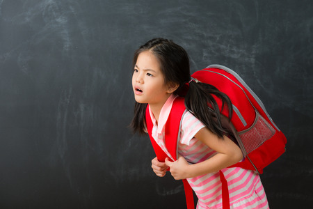 Foto de attractive cute little girl student back to school learning and carrying heavy bag feeling unhappy isolated on chalkboard background. - Imagen libre de derechos
