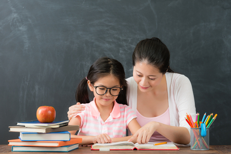 Photo for smiling young mother teaching lovely pretty preschool girl studying in chalkboard background when little daughter ready back to school accept education. - Royalty Free Image