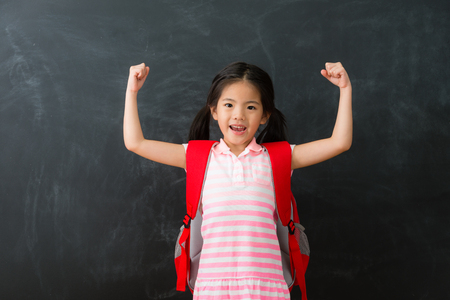 Foto de young beautiful little girl student successful finished homework ready back to school studying and standing in blackboard background raised arms looking at camera celebration. - Imagen libre de derechos