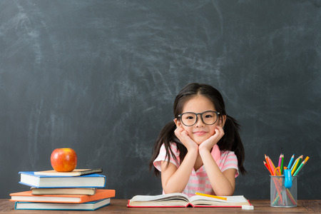Foto de lovely pretty little kid girl back to school sitting in class studying and face to camera smiling on blackboard background. - Imagen libre de derechos