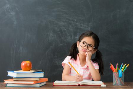 Foto de beautiful cute female children writing homework having problem and thinking about solution feeling difficulty in chalkboard background. - Imagen libre de derechos