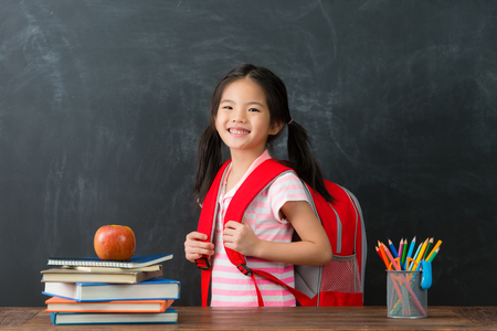 Foto de happy cheerful female kid children carrying studying bag ready back to school learning and looking at camera smiling in blackboard background. - Imagen libre de derechos
