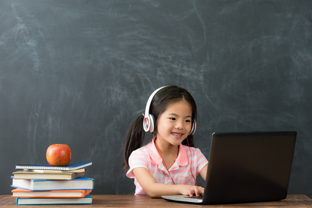 Photo for happy beautiful female student sitting in blackboard background and using mobile computer studying through online e-learning system. - Royalty Free Image