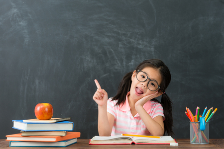 Photo for happy attractive little girl face to camera pointing air having good idea when she back to school studying in chalkboard background. - Royalty Free Image
