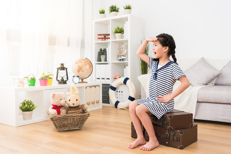 Photo pour young beauty little girl children sitting on retro suitcase looking distance when she dress up as sailor playing travel game with toys in living room. - image libre de droit