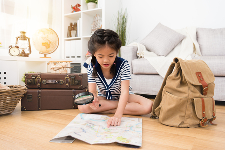 Foto de happy pretty little girl preparing personal luggage in backpack and sitting on floor using magnifier looking map ready going to adventure. - Imagen libre de derechos