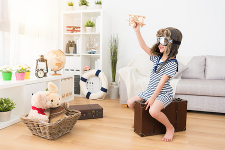 Photo pour happy pretty female kid pilot sitting on vintage suitcase and holding wooden airplane toy making fly status. - image libre de droit