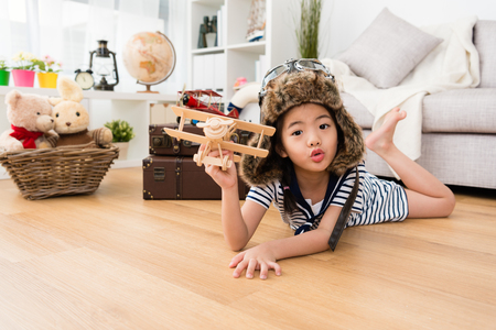 Photo for lovely pretty little girl dress up as aviator lying down on floor and playing vintage airplane and looking at camera making cute emoticon. - Royalty Free Image