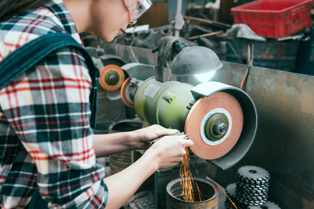 Foto de young professional female milling machine company employee wearing safety glasses working on grinding wheel and processing components with sparks in workshop. - Imagen libre de derechos