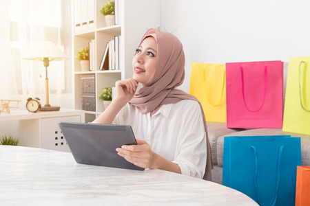 Photo pour pretty attractive muslim woman looking at air daydreaming thinking when she using mobile pad computer online shopping at home. - image libre de droit