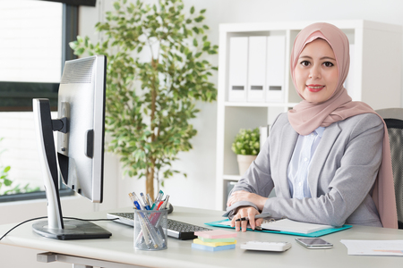 Photo pour attractive elegant female muslim business office worker working with computer and face to camera smiling. - image libre de droit