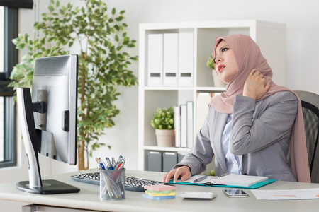 Photo pour young pretty muslim business woman sitting in office working long time feeling tired and getting neck painful using hand massaging. - image libre de droit