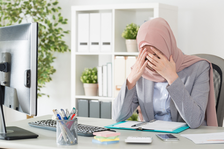 Photo pour professional young female muslim worker having problem about company cooperation case feeling sad and sitting in office thinking solution. - image libre de droit