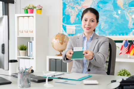 Photo pour beautiful pretty female travel agent company office worker holding passport with airline ticket and face to camera giving for client. - image libre de droit