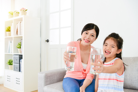 Photo pour cheerful lovely little girl kid children with mother showing healthy water face to camera. - image libre de droit