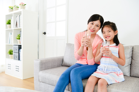 Photo pour smiling young woman and happy cute little girl sitting on sofa couch and holding glass cup with health drink water looking at camera. - image libre de droit