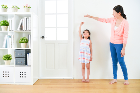 Photo pour pretty attractive mother with cute little daughter measuring growth record when they standing in wooden floor with white background together. - image libre de droit