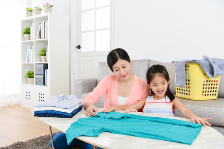 Foto de happy young little daughter helping mother folding family clothing at home and learning how to organize tidy clothes by herself. - Imagen libre de derechos