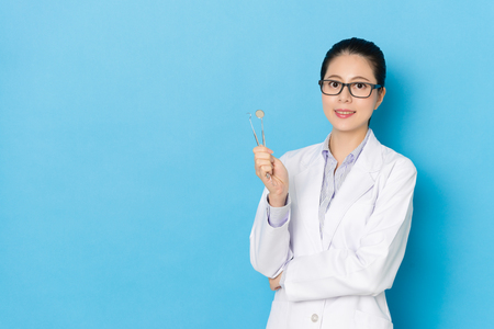 Foto de Professional young female dental doctor holding personal clinic work tool equipment standing in blue background and looking at camera smiling. - Imagen libre de derechos