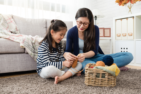Photo for beautiful Asian mom teaches her daughter how to knitting for the autumn sweater for cold season is coming in the living room at home - Royalty Free Image
