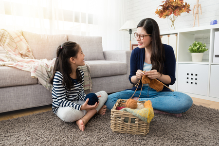 Photo for sweet Asian kids stay with her mother and enjoy knitting together sitting on the floor of the living room at home - Royalty Free Image