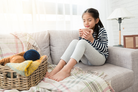 Photo pour cute Asian kids enjoy and smell hot chocolate happy to drink it sitting on the floor in the living room at home - image libre de droit