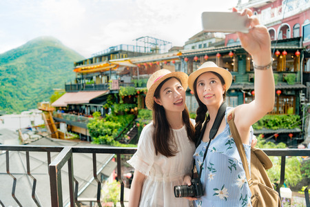 Photo pour two beautiful girls taking selfie photo of famous landmarks Amei tea house of Jiufen Taiwan. Travel holiday vacation concept. - image libre de droit