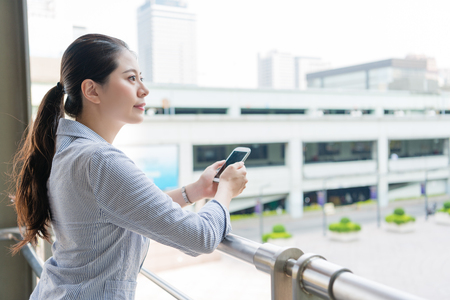 Foto de successful charming business office woman holding a mobile smart phone and looking far away vision standing outside of the office. - Imagen libre de derechos