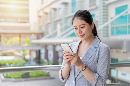 Foto de young beautiful businesswoman texting message with smartphone sms app standing outside of the office and have fun. - Imagen libre de derechos