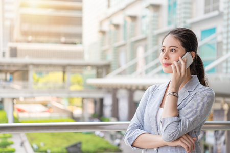 Foto de successful office woman answers the phone call from her client and looks away vision standing outside of the office. - Imagen libre de derechos