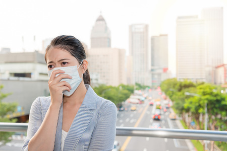 Photo for charming office lady feels sick and allergy from bad air quality pollution and wear a mask standing outside on rush hours time. - Royalty Free Image