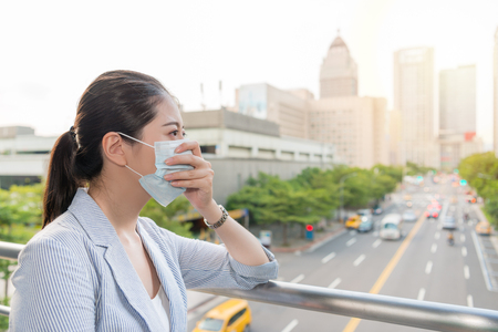 Foto de beautiful businesswoman feels allergy from bad air quality pollution and wear a mask standing outside. - Imagen libre de derechos