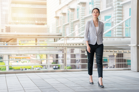 Photo for beautiful businesswoman walking on the flyover outside of office to take a rest after work. - Royalty Free Image