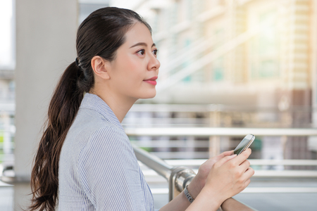 Foto de beautiful girl using looking out of future vision and holding a smartphone outside of company office. - Imagen libre de derechos