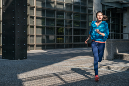 Photo pour Sport fitness running woman jogging outdoors in sport clothes on urban road. Training for marathon. - image libre de droit